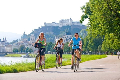 Cyclists biking along the river Salzach in Salzburg